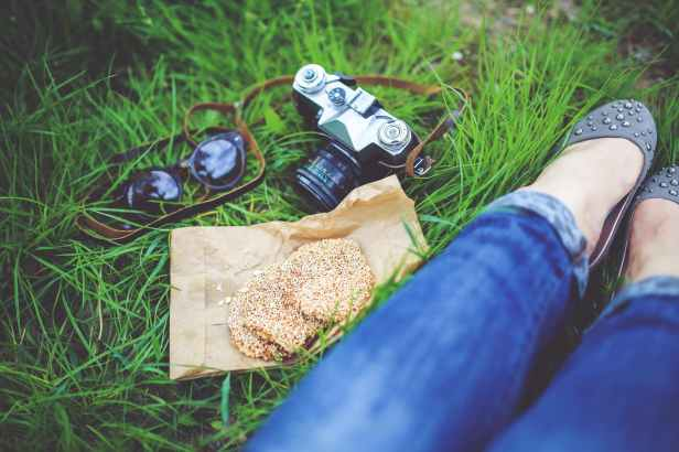 girl resting on green grass with cookies and camera