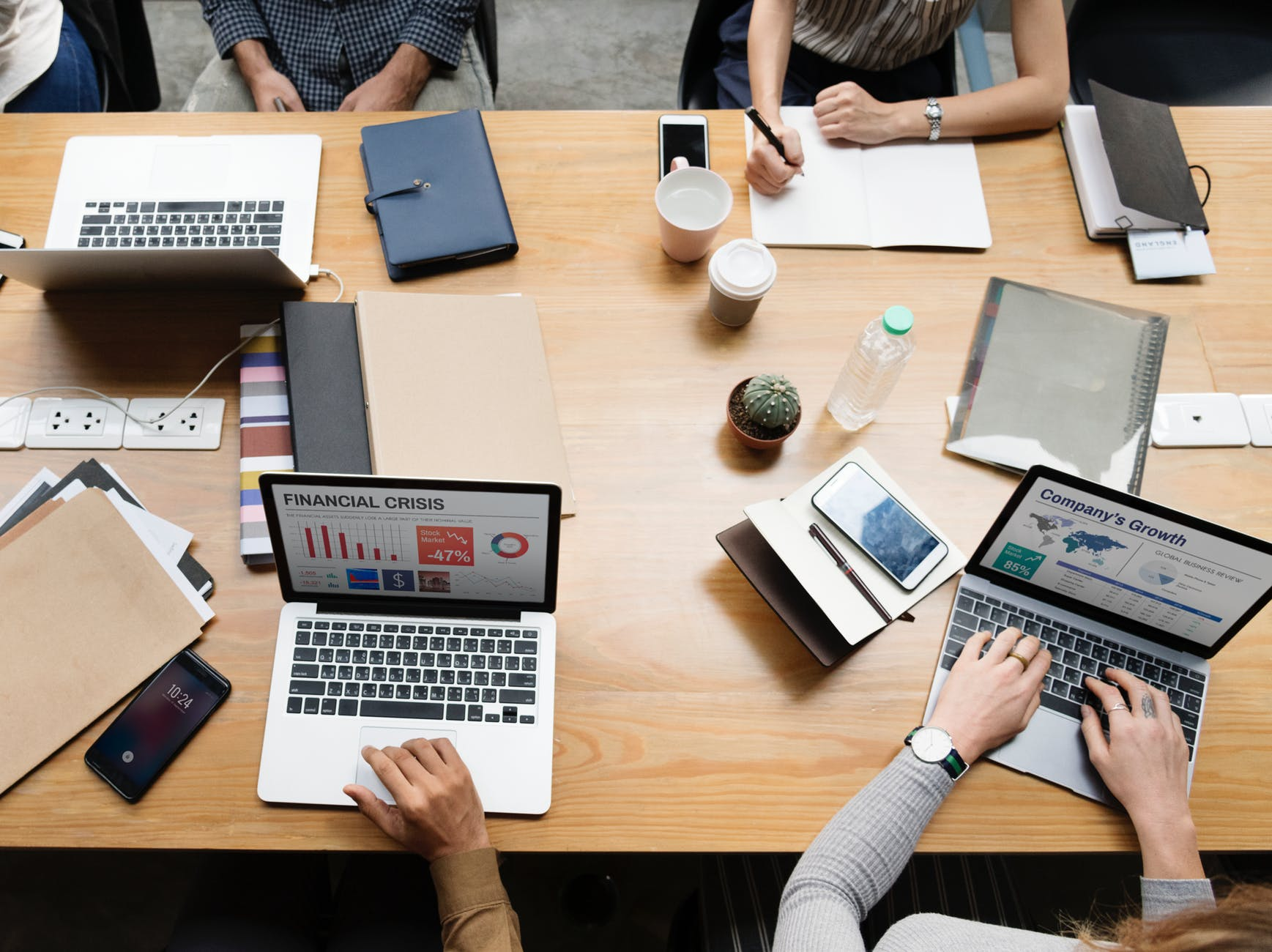 flat view photography of four persons sitting facing laptop on desk