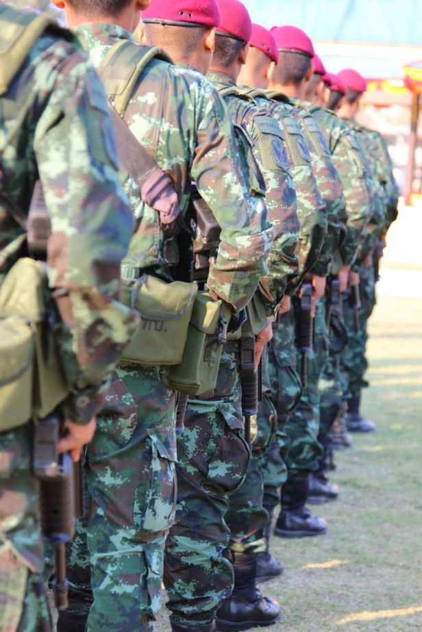 people wearing green and brown camouflage military suit while standing holding rifles