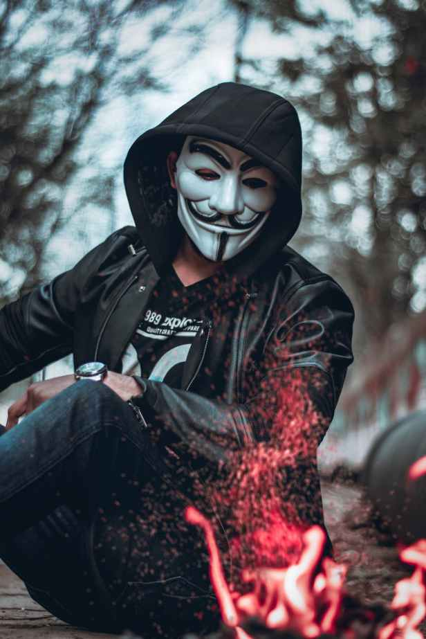 person wearing guys fawkes mask watching flame