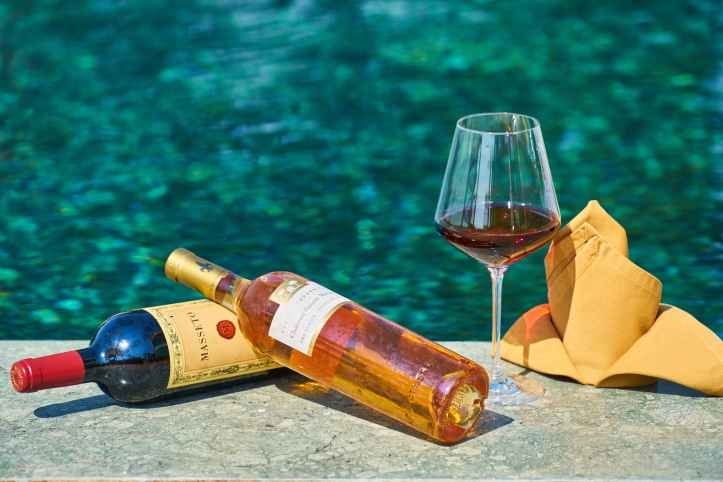 two labeled bottles of wine beside a wine glass by the pool