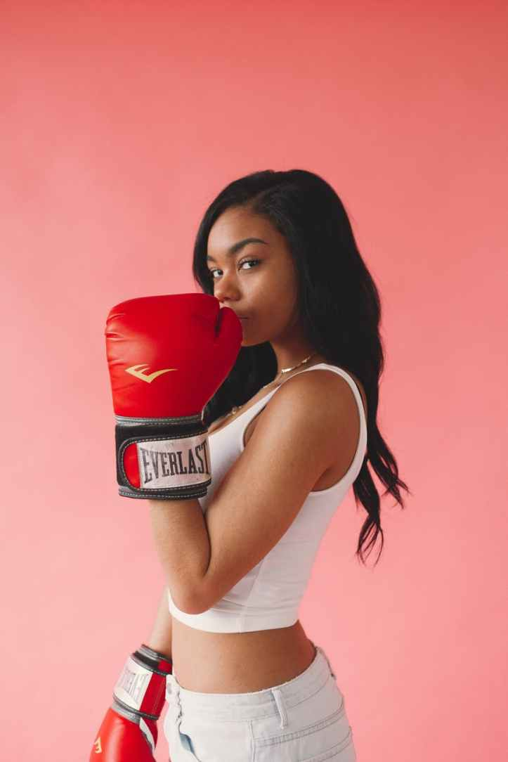 photo of woman wearing red boxing gloves