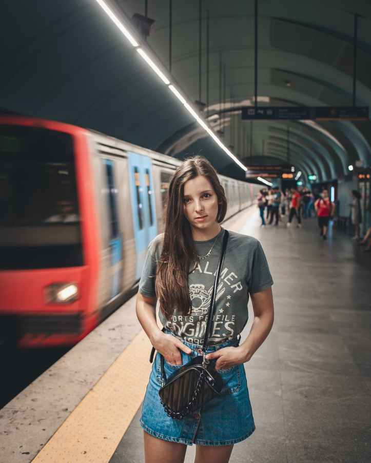 woman wearing gray crew neck t shirt and blue denim skirt standing near train in subway system